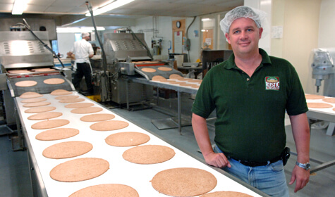 Rustic Crust owner Brad Sterl standing by pizza conveyor belt